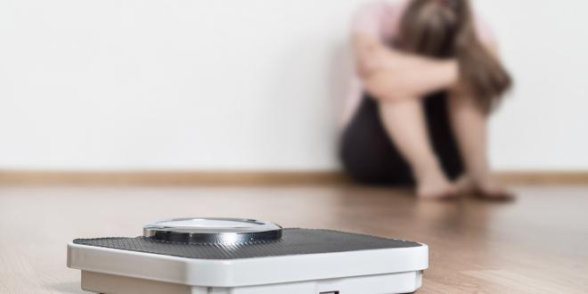 A scale on the floor with a woman sitting in the background with her head hung with failure.